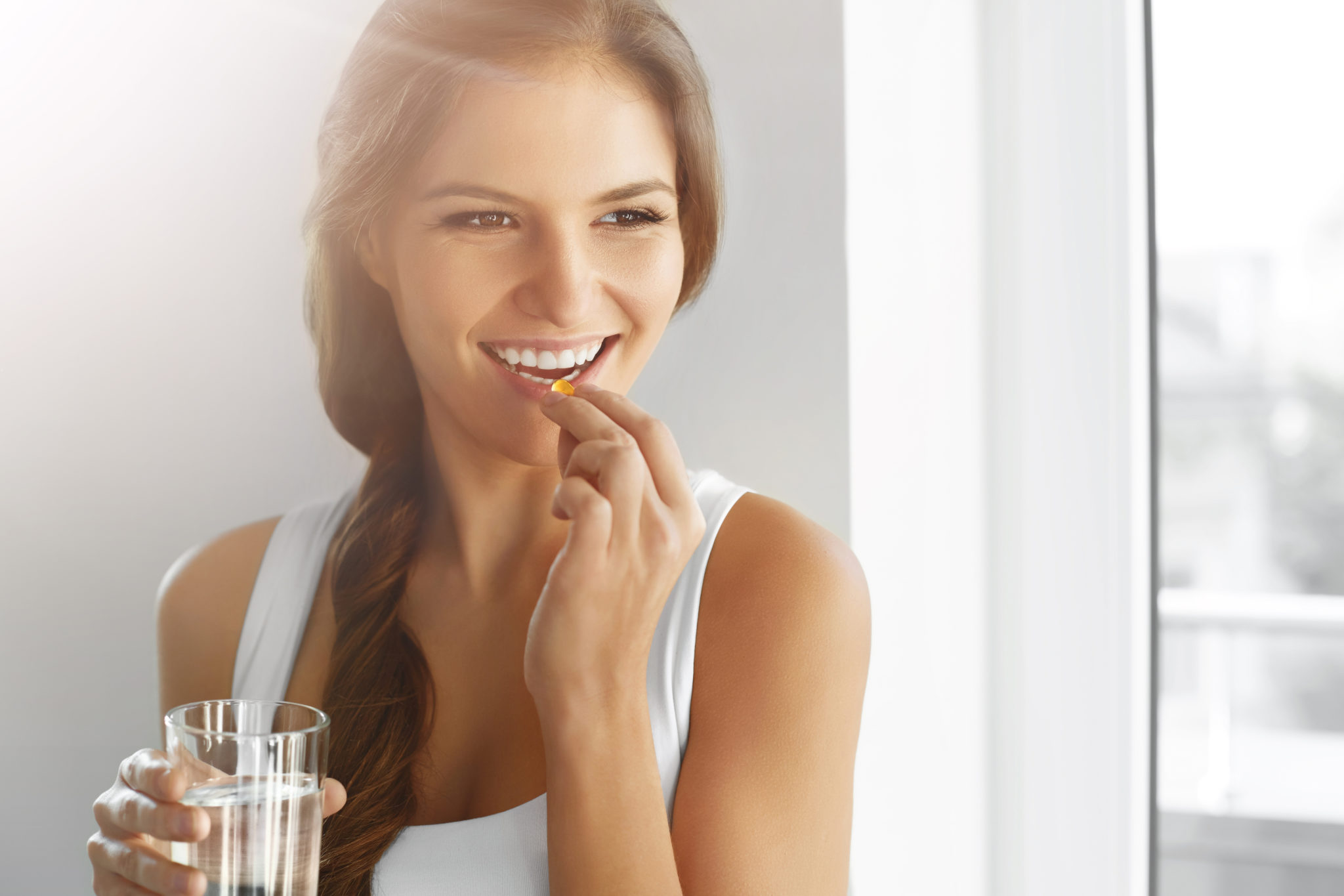 A young woman taking her daily multivitamin with a glass of water as part of a sustainable weight loss plan.